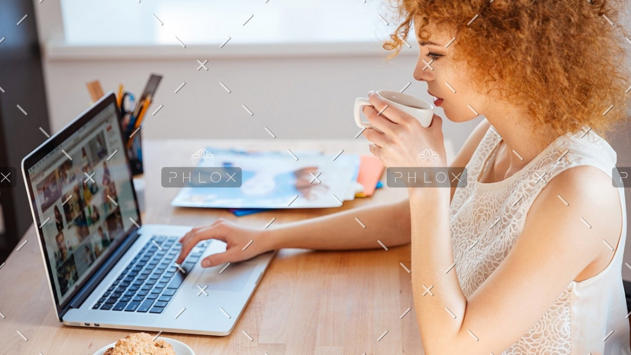 demo-attachment-410-woman-photographer-drinking-coffee-and-working-PJNBP6U